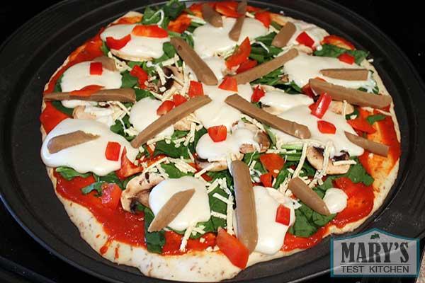 vegan pizza with vegan mozzarella cheese and vegan sausage